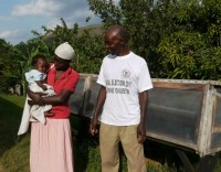 Fairtrade.banana.producer.David.Mugabi.with.wife.Dorothy.and.baby.in.front.of.solar.driers